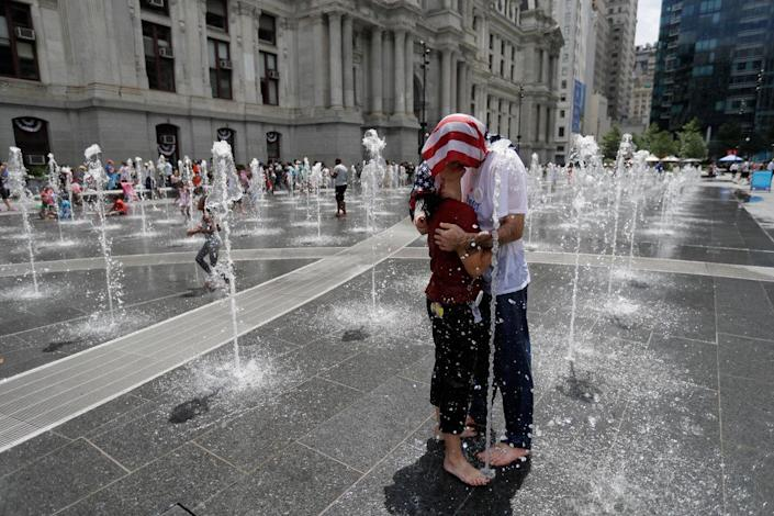 <p>Two supporters of Sen. Bernie Sanders cool off in a fountain at City Hall during a rally in Philadelphia, Tuesday, July 26, 2016, during the second day of the Democratic National Convention. (Photo: Matt Slocum/AP)</p>
