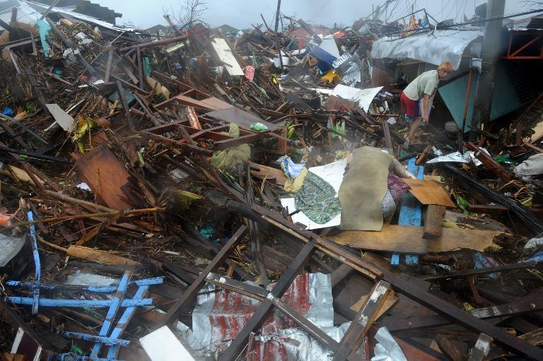 A man walks past a dead body covered with cloth among debris of destroyed houses in Tacloban, eastern island of Leyte on November 10, 2013