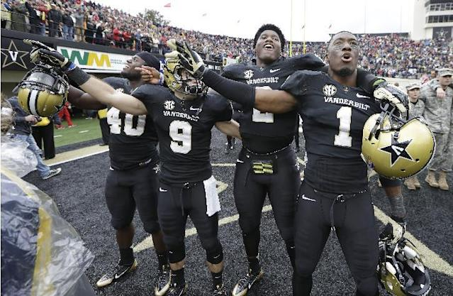 Vanderbilt players Ja'karri Thomas (40), Trent Pruitt (9), Johnny McCrary (2) and Kenny Ladler (1) celebrate after upsetting No. 15 Georgia 31-27 in an NCAA college football game on Saturday, Oct. 19, 2013, in Nashville, Tenn. (AP Photo/Mark Humphrey)