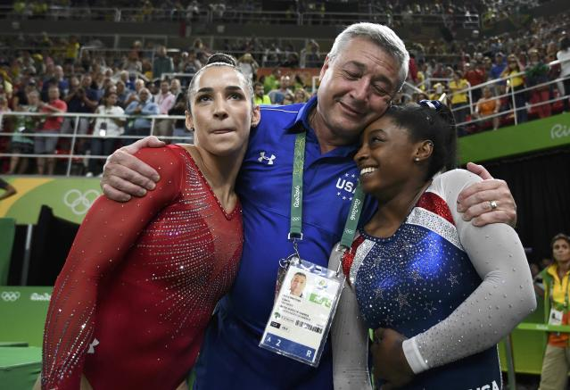2016 Rio Olympics - Artistic Gymnastics - Final - Women's Individual All-Around Final - Rio Olympic Arena - Rio de Janeiro, Brazil - 11/08/2016. Silver medal winner Alexandra Raisman (USA) of the U.S, and gold medal winner Simone Biles (USA) hug Raisman's coach Mihai Brestyan. REUTERS/Dylan Martinez FOR EDITORIAL USE ONLY. NOT FOR SALE FOR MARKETING OR ADVERTISING CAMPAIGNS.