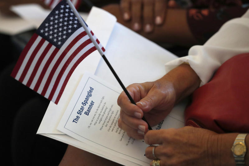 FILE - In this Aug. 16, 2019, file photo a citizen candidate holds an American flag and the words to The Star-Spangled Banner before the start of a naturalization ceremony at the U.S. Citizenship and Immigration Services Miami field office in Miami. One hundred fifty people from 40 countries took the Oath of Allegiance to become citizens during the ceremony. Foreign-born residents had higher rates of being employed than those born in the United States last year, and naturalized immigrants were more likely to have advanced degrees than the native-born, according to figures released Monday, Aug. 19, by the U.S. Census Bureau. (AP Photo/Wilfredo Lee)