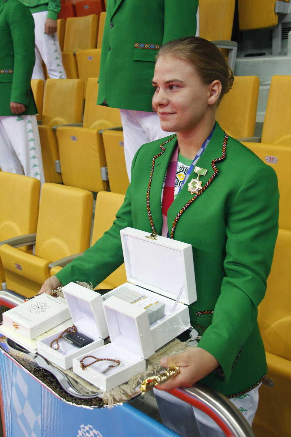 ADDS CLASS OF MEDAL Polina Guryeva, Olympic silver medalist in the women's 59kg weightlifting event, at the 2020 Summer Olympics shows her Presidential gift at a lavish ceremony in Ashgabat, Turkmenistan, Saturday, Aug. 21, 2021. Turkmenistan has lauded its first Olympic medal winner at a lavish ceremony where she was showered with gifts. Guryeva, 21, lifted a total 217 kilograms in the 59-kilogram category, edging Mikiko Andoh of Japan for second place at the Tokyo Games. (AP Photo/Alexander Vershinin)