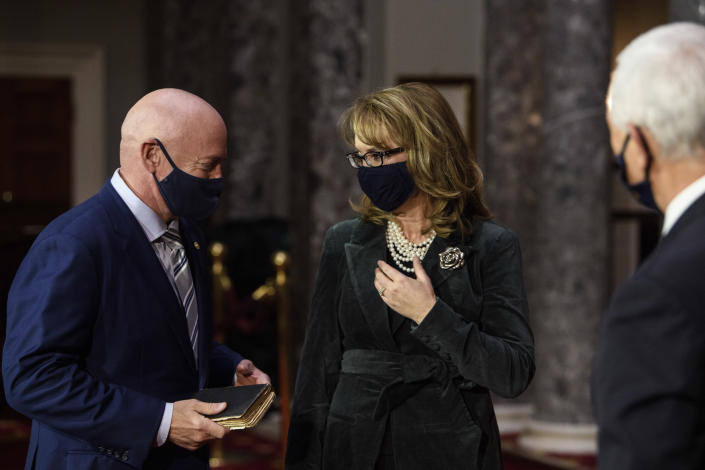 Sen. Mark Kelly, D-Ariz., talks with his wife former Rep. Gabby Giffords, D-Ariz., after participating in a re-enactment of his swearing-in Wednesday, Dec. 2, 2020, by Vice President Mike Pence in the Old Senate Chamber on Capitol Hill in Washington. (Nicholas Kamm/Pool via AP)