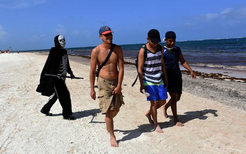 A young man disguised as the death walks at the beach of Puerto Morelos inviting tourists and locals to return to their homes -as the beaches are still closed to visitors- in Puerto Morelos, state of Quintana Roo, - Elizabeth Ruiz/AFP