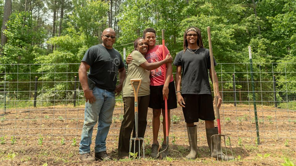 (L-R) Warren Cameron (husband), Keisha, and children Zachary and Abraham. The family owns High Hog Farm in Grayson, Georgia. (Photo: Lynsey Weatherspoon for HuffPost)