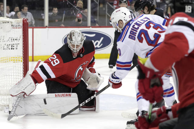 New Jersey Devils goaltender MacKenzie Blackwood (29) blocks a shot from New York Rangers left wing Connor Brickley (23) during the first period of an NHL hockey game, Monday, April 1, 2019, in Newark, N.J. (AP Photo/Julio Cortez)