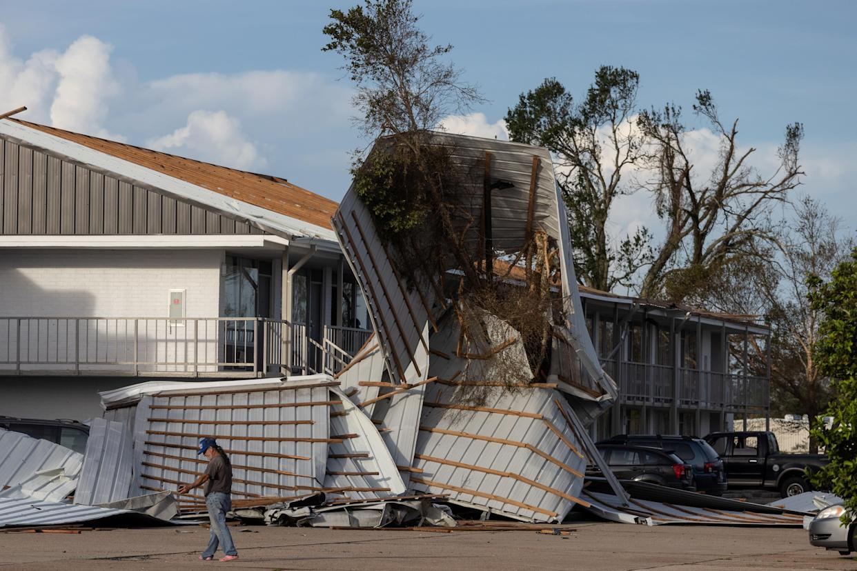 A person walks debris including a mangled section of roof that rests in a parking lot.