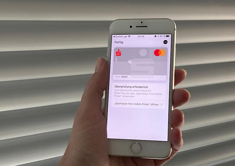 10 December 2019, Berlin: A customer of the Hamburger Sparkasse holds a mobile phone in her hand and adds her credit card to the Apple Pay payment service. On Tuesday, 371 savings banks in Germany, Commerzbank, Norisbank and LBBW, launched support for Apple's payment service. Photo: Christoph Dernbach/dpa (Photo by Christoph Dernbach/picture alliance via Getty Images)