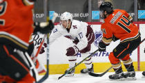 Colorado Avalanche center Tyson Jost, back left, reaches out to control the puck as Anaheim Ducks center Adam Henrique defends in the first period of an NHL hockey game Friday, March 5, 2021, in Denver. (AP Photo/David Zalubowski)