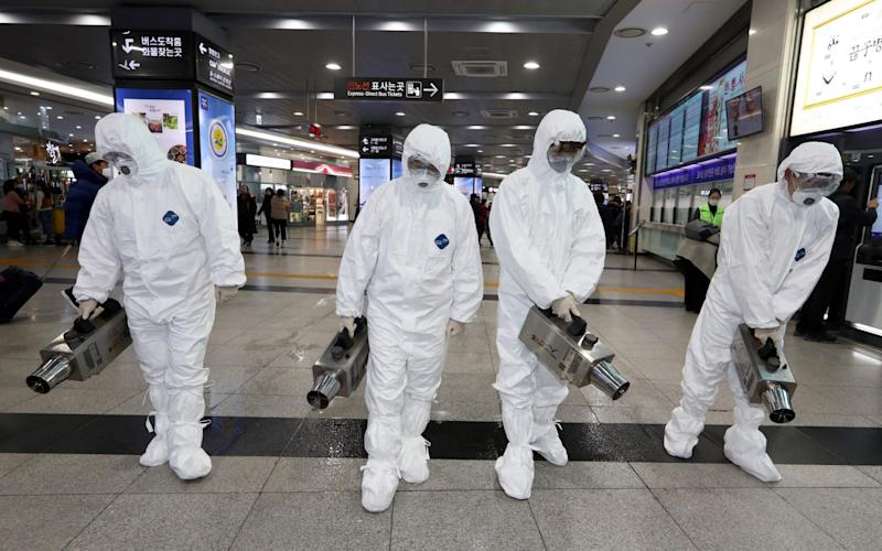 Health workers wearing protective suits spray disinfectant at a bus terminal in Gwangju as part of efforts to prevent the spread of the coronavirus - AFP