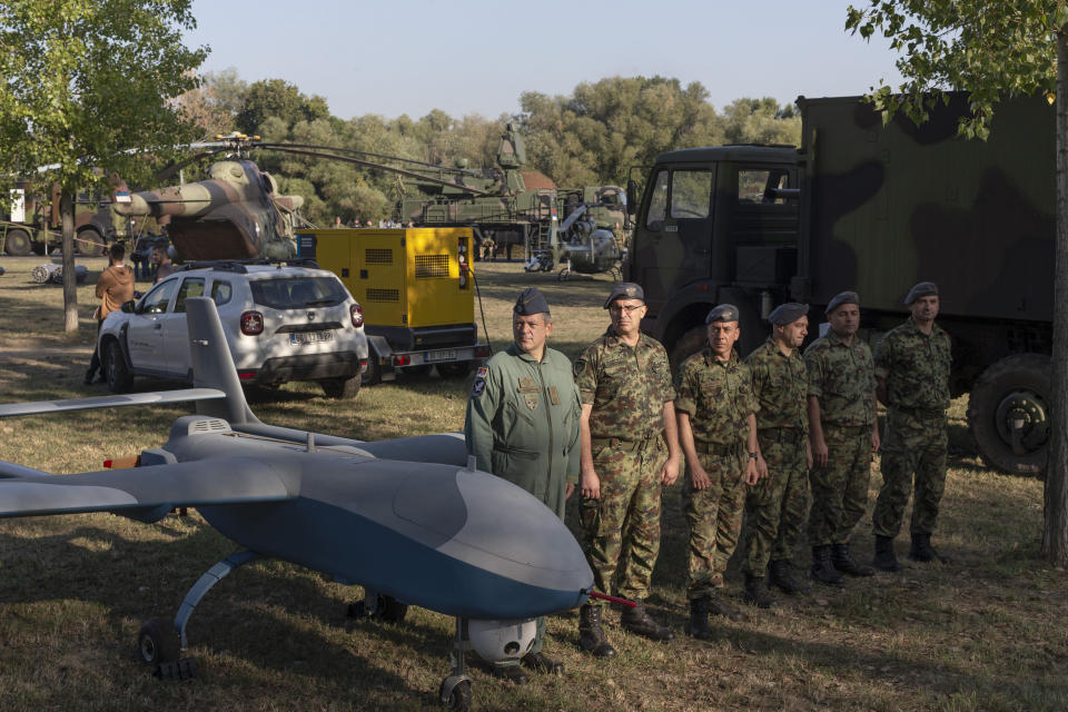 """Serbian army soldiers stand to attention next to a military drone during an arms display as part of a newly established """"Serbian Unity Day"""" holiday in Belgrade, Serbia, Wednesday, Sept. 15, 2021. Serbia has kicked off a new holiday celebrating national unity with a display of military power, triggering unease among its neighbors. The new holiday comes decades after similar calls for unity led to the bloody wars in the Balkans in the 1990s. Serbs in the region were told to display thousands of red, blue and white national flags wherever they live in the region or the world to mark """"The Day of Serb Unity, Freedom and the National Flag."""" Serbian officials are calling for the creation of a """"Serb World,"""" or political unification of an estimated 1.3 million Serbs who live in Bosnia, Montenegro, Kosovo and Croatia with Serbia. (AP Photo/Marko Drobnjakovic)"""