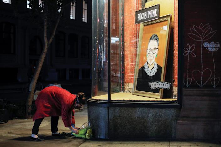 Image: A person places flowers in front of a painting in a storefront on Broadway of Associate Justice of the Supreme Court of the United States Ruth Bader Ginsburg who passed away in Manhattan, New York City (Andrew Kelly / Reuters)