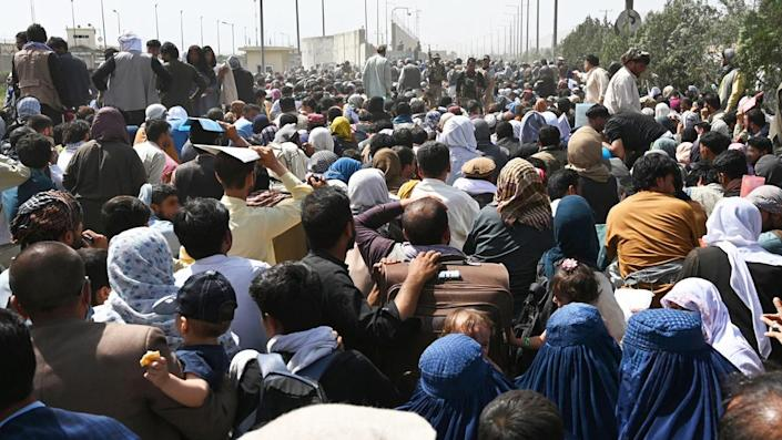 Afghans gather on a roadside near the military part of the airport in Kabul, August 20, 2021