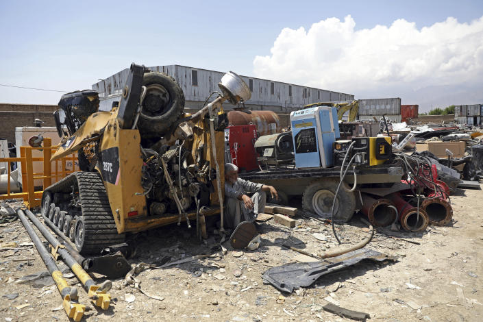 FILE - In this May 3, 2021 file photo, a man rests in the shade of destroyed machinery sold by the US military to a scrapyard, outside Bagram Air Base, in Afghanistan. In 2001 the armies of the world united behind America and Bagram Air Base, barely an hours drive from the Afghan capital Kabul, was chosen as the epicenter of Operation Enduring Freedom, as the assault on the Taliban rulers was dubbed. It's now nearly 20 years later and the last US soldier is soon to depart the base. (AP Photo/Rahmat Gul, File)