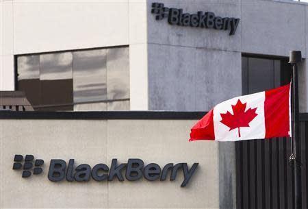 File of a Canadian flag waving in front of a Blackberry logo at the Blackberry campus in Waterloo