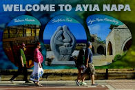 FILE - In this May 22, 2021, file photo, tourist walk at southeast resort of Ayia Napa, in the eastern Mediterranean island of Cyprus. Coronavirus infections, hospitalizations and deaths are plummeting across much of Europe. Italy and Cyprus are due to let restaurants reopen for indoor dining June 1, with discos — a big summertime moneymaker for southern European beach resorts — scheduled soon thereafter. (AP Photo/Petros Karadjias, File)