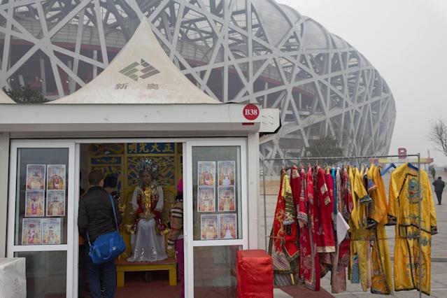 In this picture taken, Sunday, Feb. 23, 2014, a tourist dressed in traditional imperial costumes poses for photos in a booth near the iconic Bird's Nest National Stadium in Beijing, China. The National Stadium, nicknamed the Bird's Nest because of its lattice design, has become a key Beijing landmark and a favored backdrop for visitors' snapshots. But few tourists are willing to pay more than $8 to tour the facility as enthusiasm for the 2008 Games fades, and the venue has struggled to fill its space with events. Beijing, which spent more than $2 billion to build 31 venues for the 2008 Summer Games, is reaping some income and tourism benefits from two flagship venues, though many sites need government subsidies to meet hefty operation and maintenance costs. (AP Photo/Ng Han Guan)