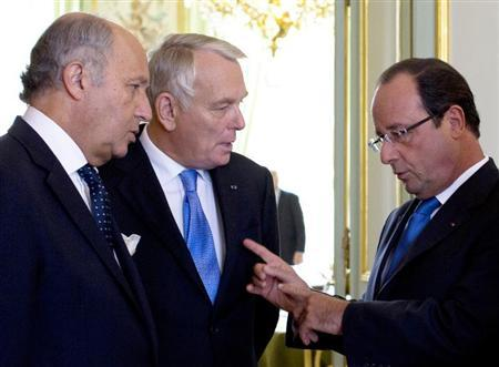 France's President Hollande speaks with French Foreign Minister Fabius and Prime Minister Ayrault before a National Security Council meeting at the Elysee Palace in Paris