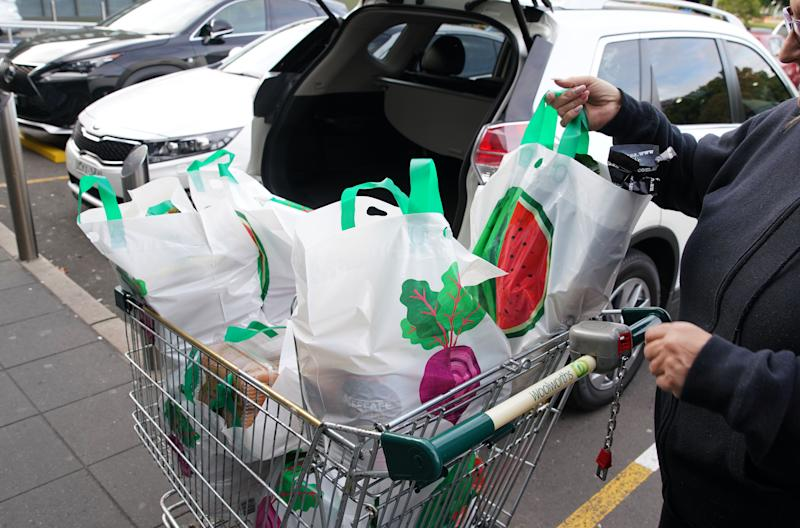 A stock image of a shopper with a trolley full of reusable Woolworths bags.