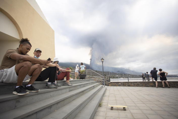 People sit on some steps as others look at the eruption of a volcano near El Paso on the island of La Palma in the Canaries, Spain, Monday, Sept. 20, 2021. Lava continues to flow slowly from a volcano that erupted in Spain's Canary Islands off northwest Africa. Officials say they are not expecting any other eruption and no lives are currently in danger. (AP Photo/Gerardo Ojeda)
