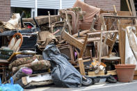 A pile of discarded furniture stands in front of a house in the district of Blessem, in Ergfstadt, Germany, Thursday July 22, 2021. In the flood disaster area of Erftstadt-Blessem, some residents are being allowed back into their homes to clear debris after heavy rains caused devastating floods. (Marius Becker/dpa via AP)
