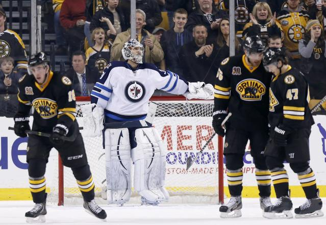 Winnipeg Jets' Ondrej Pavelec, center, stands in the goal as Boston Bruins' Johnny Boychuk (55) and Torey Krug (47) celebrate a goal by teammate Reilly Smith, left, in the third period of an NHL hockey game in Boston, Saturday, Jan. 4, 2014. The Bruins won 4-1. (AP Photo/Michael Dwyer)