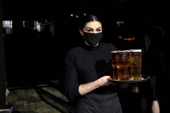 A member of the bar staff carries drinks to outdoor tables at the reopening of the Figure of Eight pub, in Birmingham, England, Monday April 12, 2021. Millions of people in England will get their first chance in months for haircuts, casual shopping and restaurant meals on Monday, as the government takes the next step on its lockdown-lifting road map. (Jacob King/PA via AP)