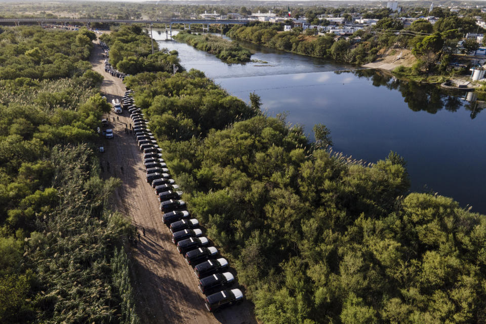 FILE - In this Wednesday, Sept. 22, 2021, file photo, a line of Texas Department of Safety vehicles line up on the Texas side of the Rio Grande with Mexico visible, right, near an encampment of migrants, many from Haiti, in Del Rio, Texas. The U.S. is flying Haitians camped in a Texas border town back to their homeland and blocking others from crossing the border from Mexico. On Friday, the camp on the U.S. side that once held as many as 15,000 mostly Haitian refugees was completely cleared. (AP Photo/Julio Cortez, File)