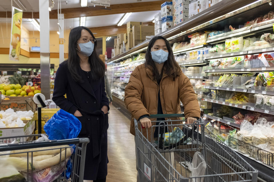 Two women wear surgical masks while shopping at a grocery store in Cupertino, California. (Photo by Yichuan Cao/NurPhoto via Getty Images)