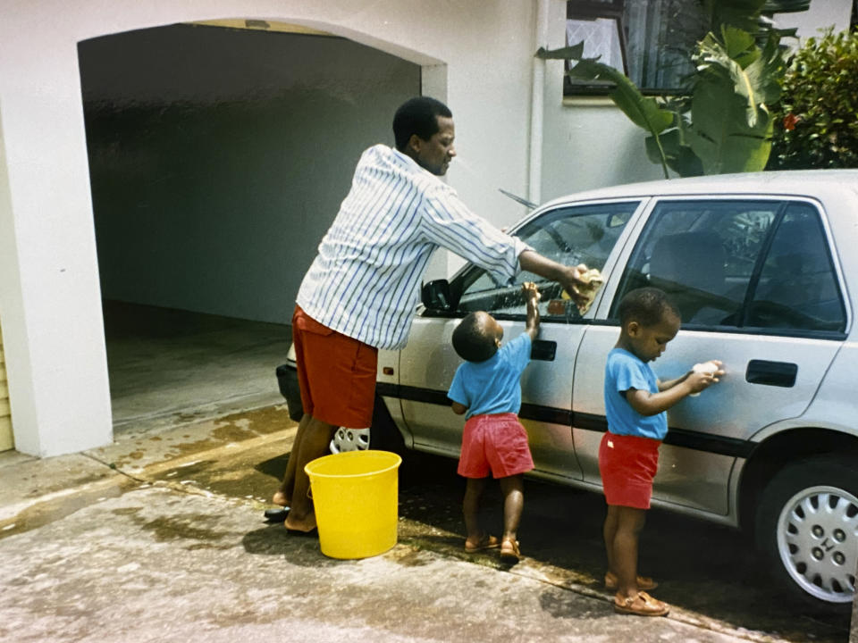 In this photo supplied courtesy of the Mini family, the late South African doctor and activist Dr. Clarence Mini, washes his car with his children in the early 1990's. Clarence Mini, a South African activist and doctor who died of COVID-19 spent his life fighting apartheid, the government's denial of HIV/AIDS and rampant corruption. Loved ones say Mini knew the odds were against him but he was committed to what he believed was right. He died in May at age 69. (Photo courtesy of the Mini family via AP)