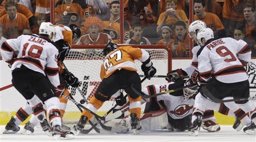 Philadelphia Flyers' Maxime Talbot (27) scores a goal past New Jersey Devils goalie Martin Brodeur (30) as Devils' Travis Zajac (19) and Zach Parise (9) defend in the first period of Game 5 of a second-round NHL hockey Stanley Cup playoff series, Tuesday, May 8, 2012, in Philadelphia. (AP Photo/Matt Slocum)