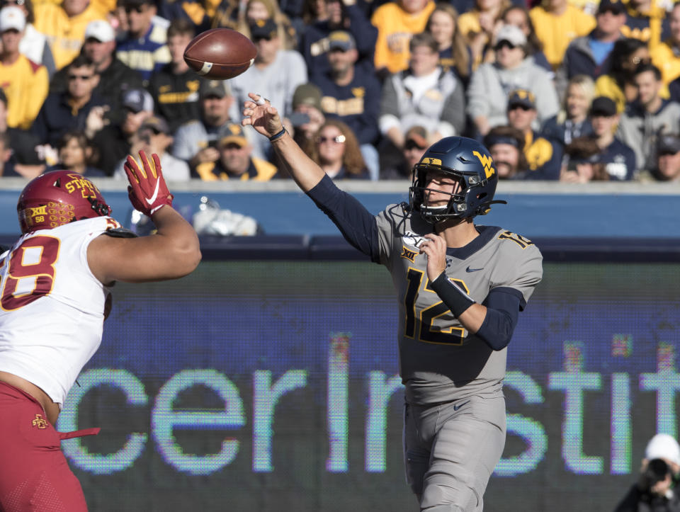 West Virginia quarterback Austin Kendall (12) attempts a pass during the first half of an NCAA college football game against Iowa State Saturday, Oct. 12, 2019, in Morgantown, W.Va. (AP Photo/Raymond Thompson)