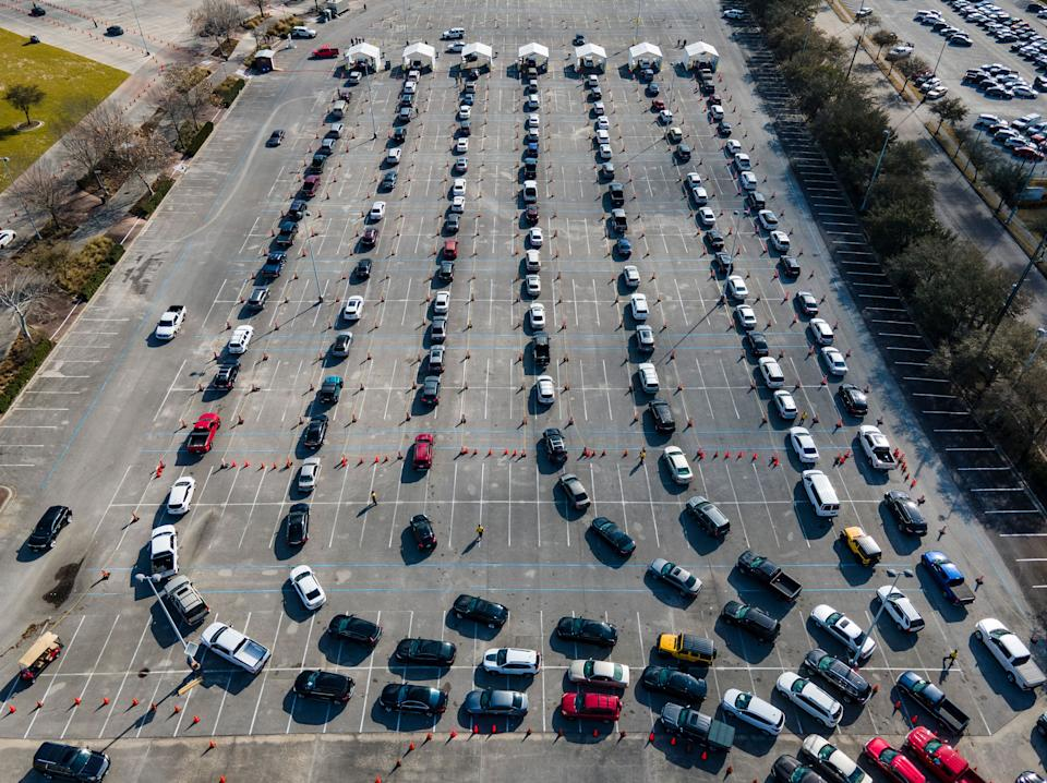Cars line up in a parking lot at NRG Park in Houston as people wait to receive a COVID-19 vaccines at the federally supported supersite Thursday. (Photo: Mark Mulligan/Houston Chronicle via Associated Press)