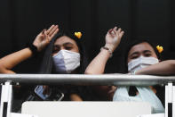 Two women flash three-finger protest gestures while wearing headbands adorned with yellow ducks, which have become a good-humored symbol of resistance during anti-government rallies, Friday, Nov. 27, 2020 in Bangkok, Thailand. Pro-democracy demonstrators are continuing their protests calling for the government to step down and reforms to the constitution and the monarchy, despite legal charges being filed against them and the possibility of violence from their opponents or a military crackdown. (AP Photo/Wason Wanichakorn)