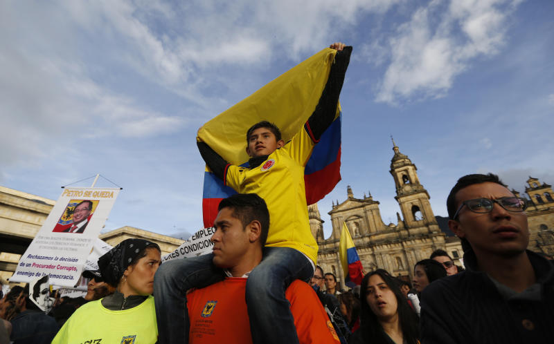 Supporters of Bogota's Mayor Gustavo Petro rally against Colombia's inspector-general Alejandro Ordonez in Bogota, Colombia, Friday, Dec. 13, 2013. Ordonez has ordered Petro removed from office over alleged mismanagement of the garbage-collection system. (AP Photo/Fernando Vergara)