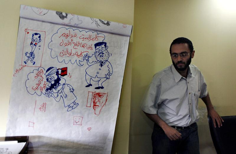 """Egyptian cartoonist Abdul-Rahman Najmuddin walks past cartoon sketches, one depicting Egyptian president Mohammed Morsi with a caption in Arabic """"someone calls home and tell them that I am delivering a speech,"""" at his office in the Egyptian Al Watan daily newspaper headquarters in Cairo, Egypt, Wednesday, Sept. 26, 2012. Amid outrage sparked by perceived insults to Islam, one Egyptian newspaper has decided to fight cartoons with cartoons. Al Watan daily says it is responding to the crude caricatures published last week by a satirical Parisian weekly in kind: a series of sketches critiquing relations between the Arab world and the West. The paper says they are a """"civilized"""" alternative to the violent protests across the Muslim world sparked by a low-budget anti-Islam film produced in the United States. (AP Photo/Nasser Nasser)"""