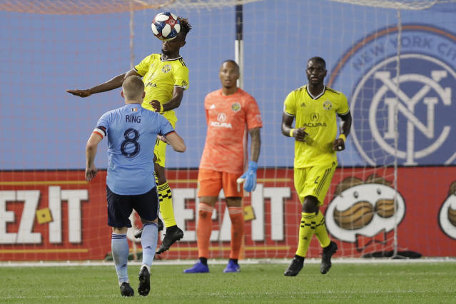 Columbus Crew defender Harrison Afful (25) heads the ball out of the area near the Crew's goal as New York City FC midfielder Alexander Ring (8) defends during the second half of an MLS soccer match, Wednesday, Aug. 21, 2019, in New York. New York City FC defeated Columbus 1-0. Columbus Crew SC goalkeeper Elroy Room, second from right, and Columbus midfielder Luis Argudo, right, watch. (AP Photo/Kathy Willens)