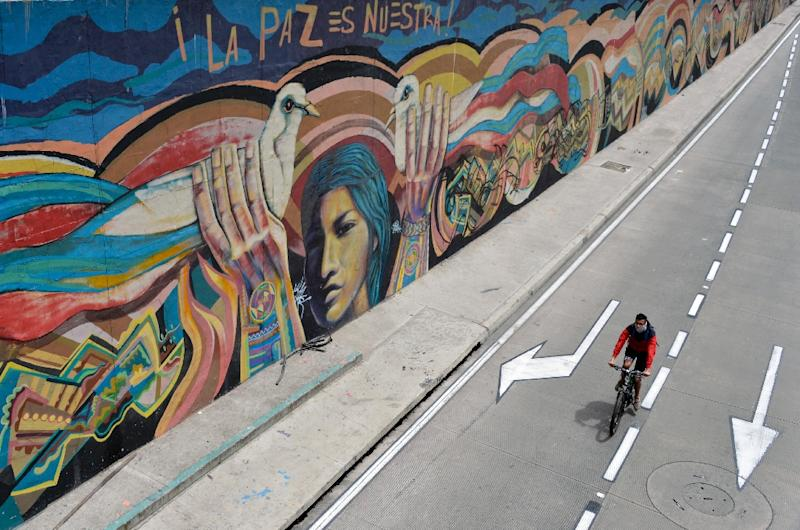 """A man rides his bike past a graffiti that reads """"Peace is ours"""" in Bogota, Colombia (AFP Photo/Guillermo Legaria)"""