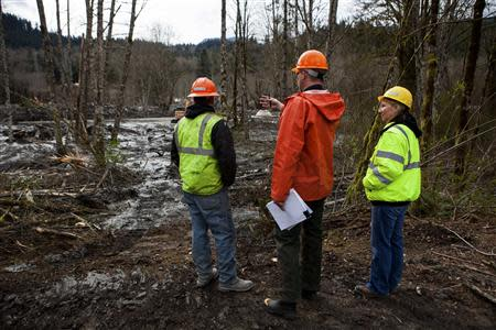 Snohomish County officials evaluate the scene left by a mudslide in Oso, Washington, April 3, 2014. REUTERS/Max Whittaker