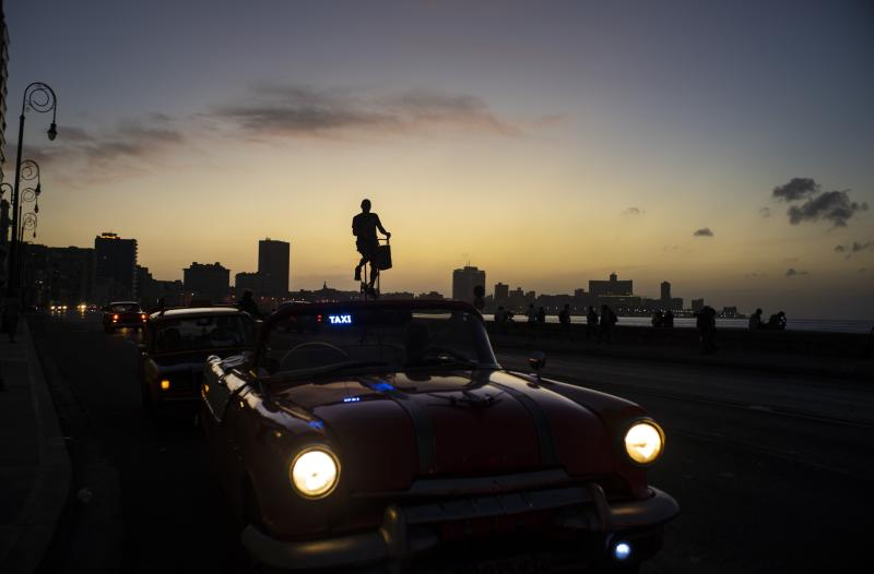 Felix Girola rides his 11-foot tall, custom-made bicycle in Havana, Cuba, Thursday, Feb. 6, 2020. Ever since he was a child, Girola dreamed of riding tall bicycles. For the past 35 years he's been able to live his dream on the streets of Cuba, winding his way, in tall fashion, between pedestrians and classic cars. (AP Photo/Ramon Espinosa)
