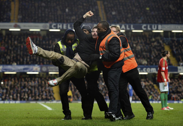 A football fan is carried off the pitch by security personnel after running on the field as Chelsea take on Swansea City during their English League Cup semi-final soccer match at Stamford Bridge in London January 9, 2013. REUTERS/Dylan Martinez (BRITAIN - Tags: SPORT SOCCER TPX IMAGES OF THE DAY CAPITAL ONE CUP)