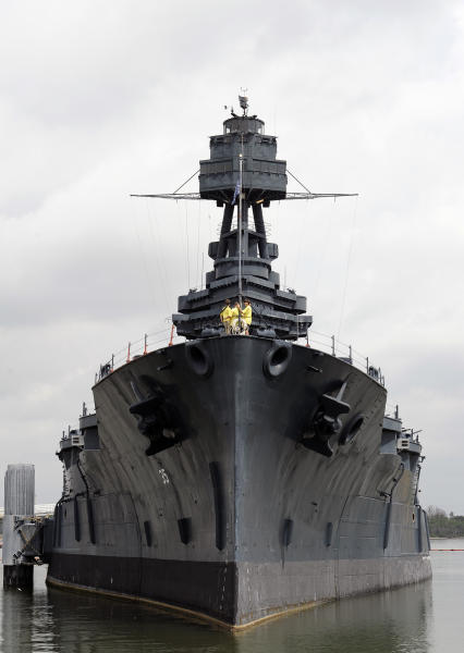 Tourists visit the deck of the USS Texas as she lists slightly on the port side Wednesday, June 13, 2012, in Houston. The 100-year-old battleship's hull sprung a leak five days ago and she has been taking on as much as 1,000 gallons of seawater every minute as workers struggle to contain it. (AP Photo/Pat Sullivan)