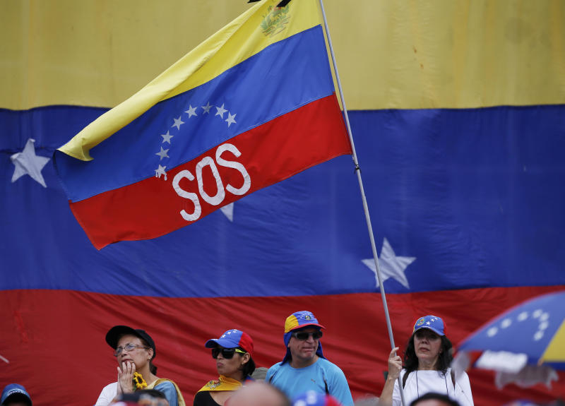 "A supporter of Venezuela's opposition leader and self-proclaimed interim president Juan Guaidó, waves a Venezuelan flag marked with the letters ""SOS"", during a rally in Caracas, Venezuela, Saturday, May 11, 2019. Guaidó has called for nationwide marches protesting the Maduro government, demanding new elections and the release of jailed opposition lawmakers. (AP Photo/Fernando Llano)"