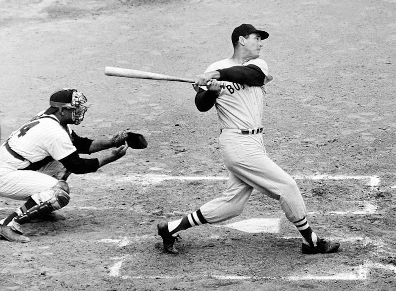 """FILE - In this April 18, 1960, file photo, Ted Williams of the Boston Red Sox knocks the ball out of the park for a home run in the second inning against the Washington Senators. The Washington catcher is Earl Battey. A new film explores the life of baseball legend Williams who struggled with his Mexican-American heritage and his volatile relationship with his family and the press. The upcoming PBS """"American Masters"""" documentary on the former Boston Red Sox slugger uses rare footage and family interviews to paint a picture of a complicated figure that hid his past but later spoke out and defended black players. (AP Photo/File)"""