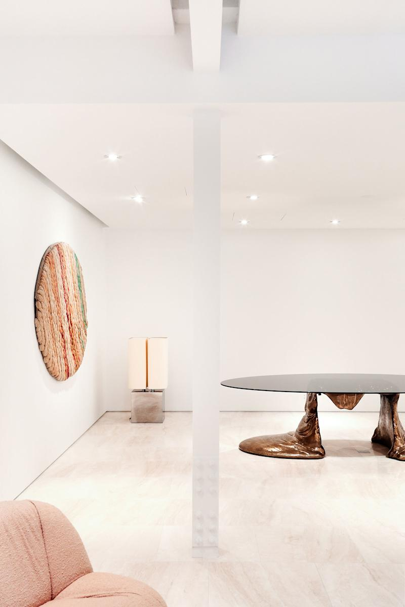 A Manhattan gallery with travertine floors and works by Pierre Paulin, Sheila Hicks, Michel Boyer, and César (clockwise from bottom left).