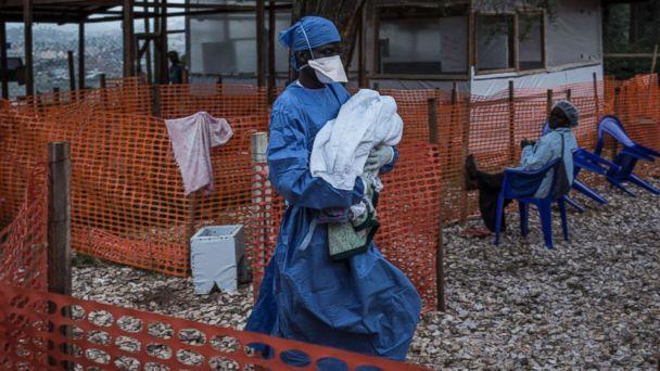 PHOTO: A caretaker already cured of Ebola is seen carrying a four day old baby suspected of having Ebola into a Medecins Sans Frontieres supported Ebola treatment center in Butembo, Congo, Nov. 4, 2018. (John Wessels/MSF via AP)