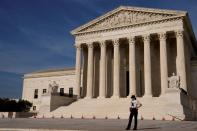 FILE PHOTO: A U.S. Supreme Court police officer patrols the plaza in front the court building in Washington