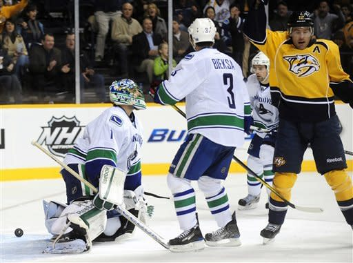 Nashville Predators center Mike Fisher, right, reacts after a goal by Nashville Predators left wing Sergei Kostitsyn gets past Vancouver Canucks goalie Roberto Luongo (1) and Canucks defenseman Kevin Bieksa (3) in the second period of an NHL hockey game on Tuesday, Feb. 7, 2012, in Nashville, Tenn. (AP Photo/Mike Strasinger)