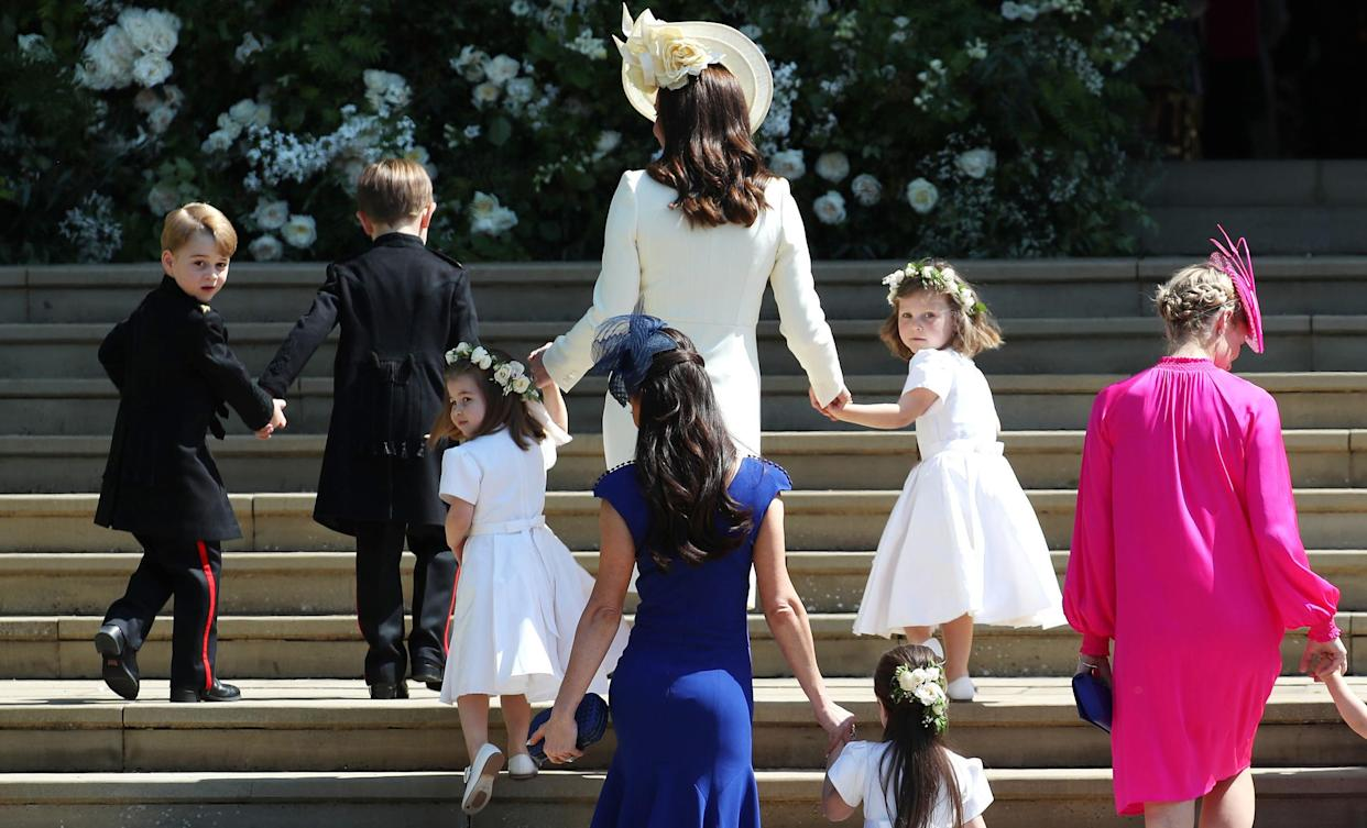 Britain's Catherine, Duchess of Cambridge (C) walks up the west steps with Prince George (L) and Princess Charlotte (3L) and bridesmaids for the wedding ceremony of Britain's Prince Harry, Duke of Sussex and US actress Meghan Markle at St George's Chapel, Windsor Castle, in Windsor, on May 19, 2018. (Photo by Jane Barlow / POOL / AFP)        (Photo credit should read JANE BARLOW/AFP via Getty Images)