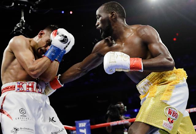 Terence Crawford, left, punches England's Amir Khan during the fourth round of a WBO world welterweight championship boxing match Sunday, April 21, 2019, in New York. Crawford won the fight. (AP Photo/Frank Franklin II)